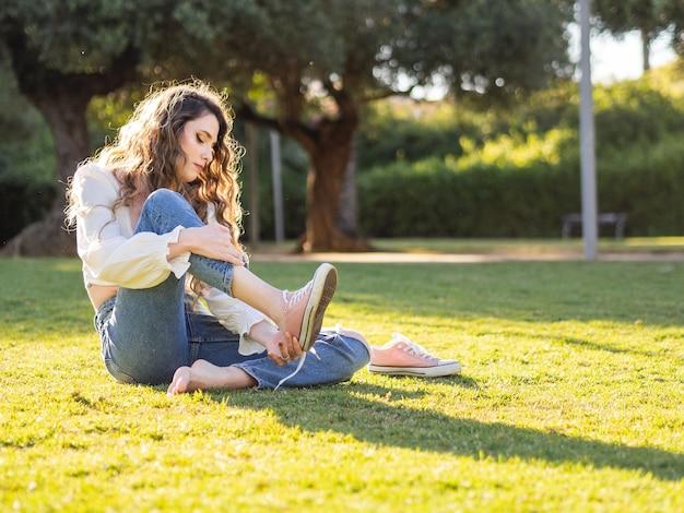 Hübsche junge langhaarige frau, die auf dem gras im park sitzt, zieht ihre turnschuhe aus