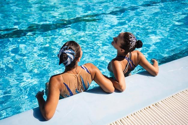 Hübsche junge mädchen, die sich am pool entspannen