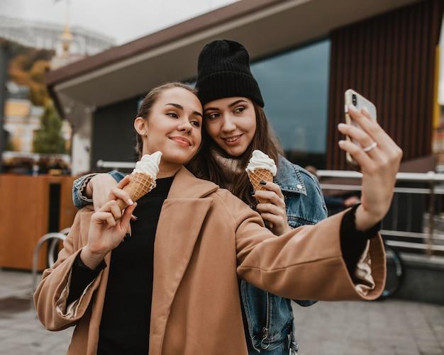 Hübsche junge mädchen, die zusammen ein selfie machen