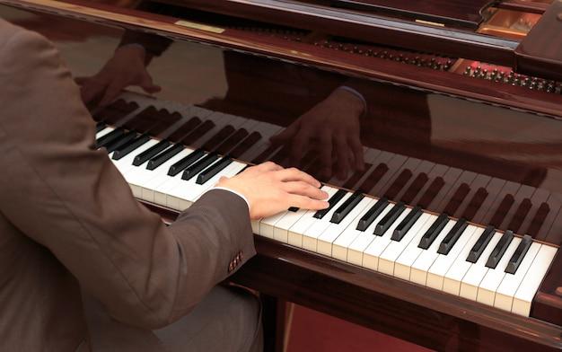 Hübsche junge männer, die klavier spielen