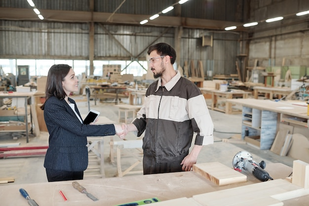 Hübsche junge managerin oder geschäftspartnerin, die dem arbeiter der möbelfabrik nach verhandlung im großen lager die hand schüttelt