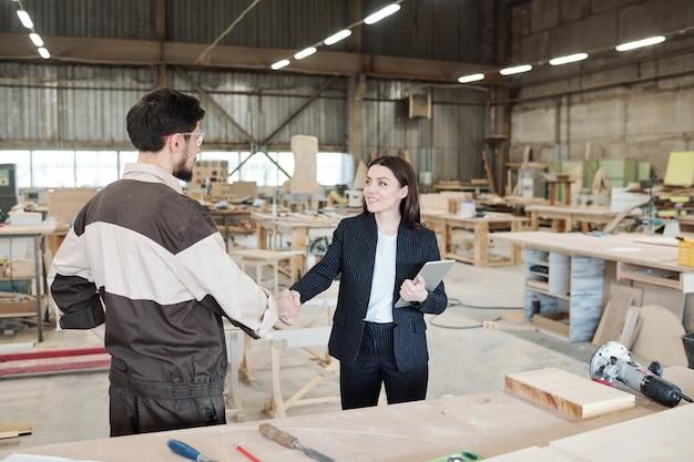 Hübsche junge managerin oder geschäftspartnerin, die nach verhandlungen in einem großen lager die hand des arbeiters der möbelfabrik schüttelt