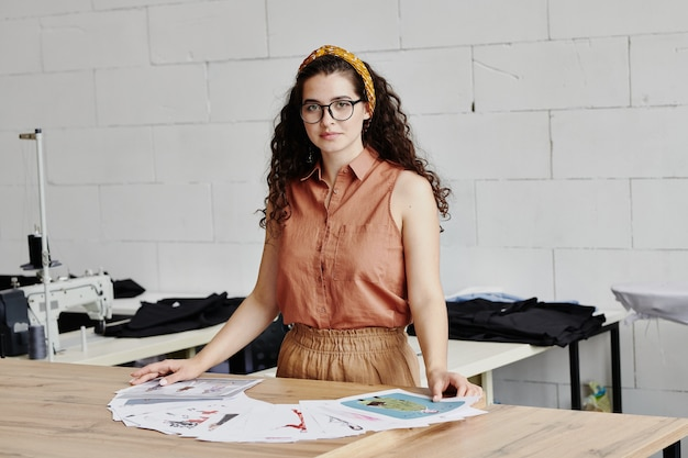 Hübsche junge modedesignerin mit dunklem, langem, welligem haar, das mit skizzen am tisch steht und einige für eine neue kollektion auswählt