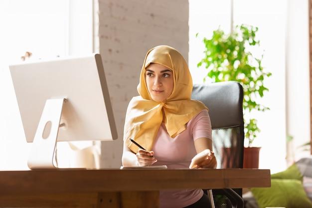 Hübsche junge muslimische frau zu hause während der quarantäne und selbstisolierung, mit tablet für selfie oder videoanruf, online-unterricht