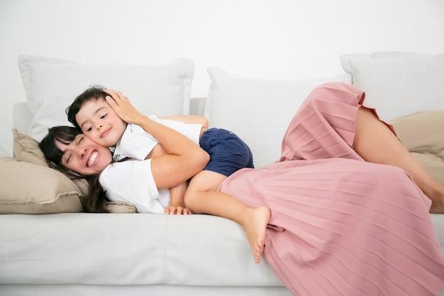 Hübsche junge mutter, die auf sofa liegt und niedlichen sohn mit liebe umarmt.