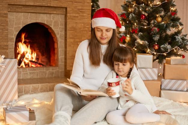Hübsche junge mutter, die buch zu ihrer tochter liest, während sie nahe kamin und tannenbaum im festlichen wohnzimmer sitzt