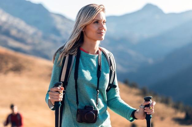 Hübsche junge reisende mit rucksack, die beim gehen auf den berg zur seite schaut.
