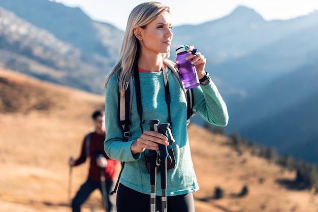 Hübsche junge reisende mit rucksack, die beim trinken von wasser auf dem berg zur seite schaut.