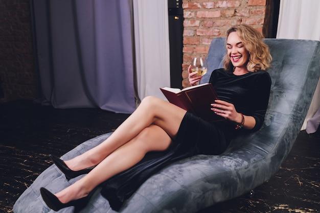 Hübsche junge rothaarige frau, die ein buch liest, das auf einem schwarzen ledersofa mit einem glas oder rotwein liegt.