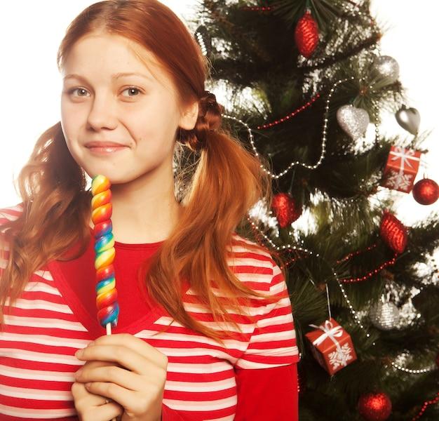 Hübsche junge rothaarige frau, die lolly pop hält. weihnachtsbaum.