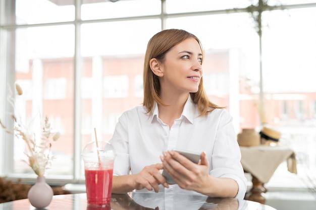 Hübsche junge ruhige frau, die im smartphone rollt, während sie im café sitzt, etwas trinkt und waren im online-shop auswählt