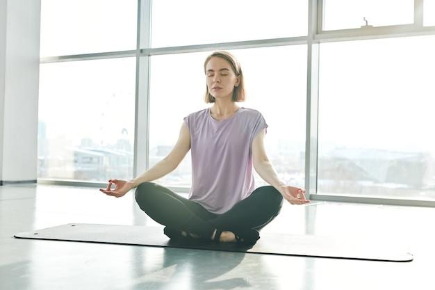 Hübsche junge ruhige frau in der aktivkleidung, die auf matte sitzt, während lotusstellung während des yoga-trainings im fitnessstudio oder im freizeitzentrum übt