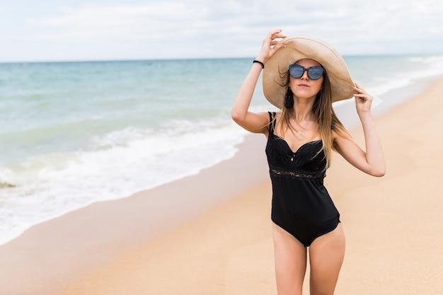 Hübsche junge schönheitsfrau mit hut und sonnenbrille am strand