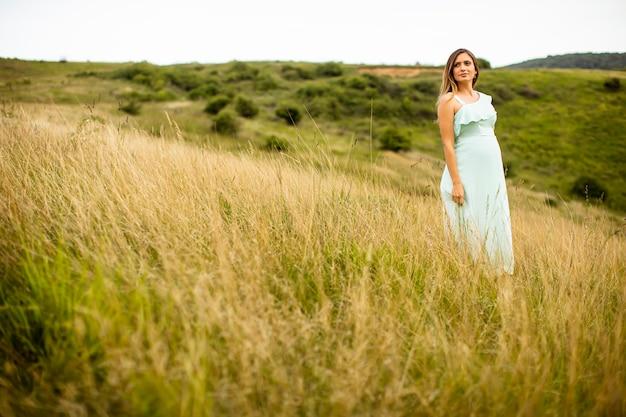 Hübsche junge schwangere frau, die draußen in der natur am sommertag entspannt
