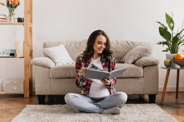Hübsche junge schwangere frau in jeanshosen und weißem t-stück liest buch