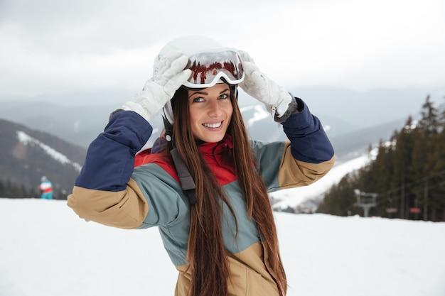 Hübsche junge snowboarderin auf der piste frostigen wintertag