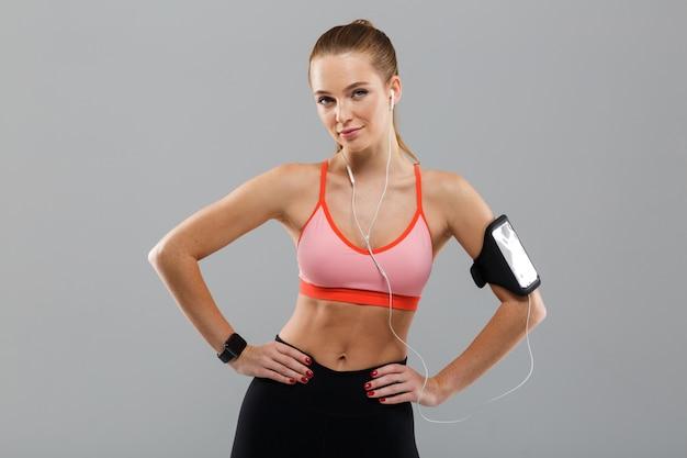 Hübsche junge sportfrau, die musik per handy hört