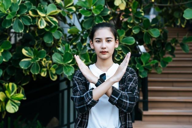 Hübsche junge stehende frau zeigt ihr handzeichenkreuz auf der treppe eines einkaufszentrums shopping