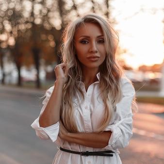 Hübsche junge stilvolle frau im trendigen weißen hemd in der stadt draußen bei sonnenuntergang