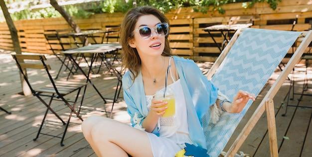 Hübsche junge stilvolle frau mit überraschtem gesichtsausdruck, der im sommeroutfit im liegestuhl sitzt, weißes kleid, blauen umhang, sonnenbrille, geldbörse trägt, frischen saft trinkt, sich entspannt