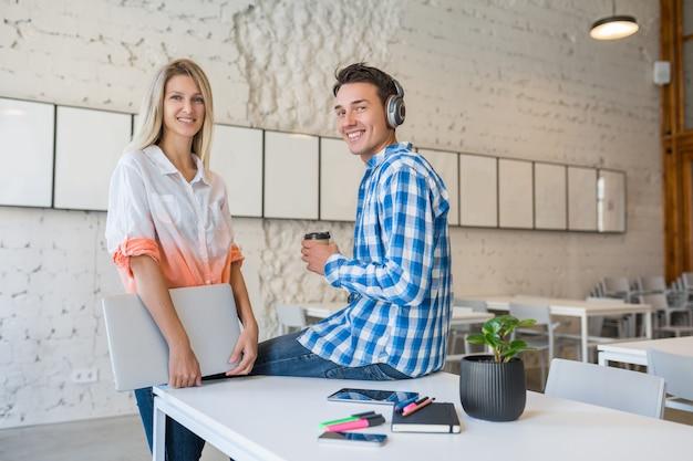 Hübsche junge stilvolle glückliche leute im zusammenarbeitenden büro,