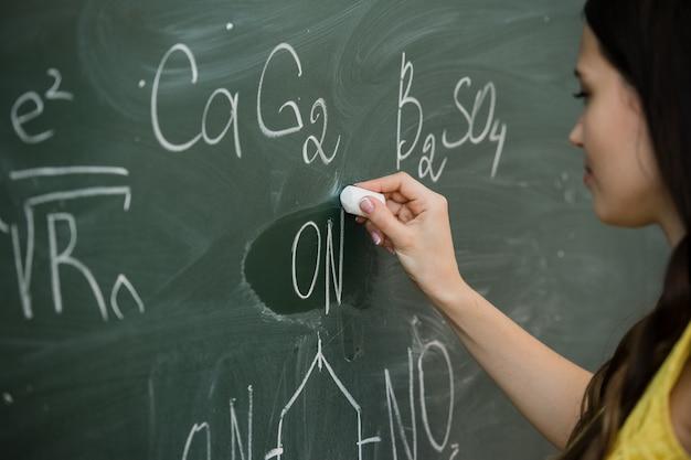 Hübsche junge studentin, die während eines chemieunterrichts an die tafel schreibt