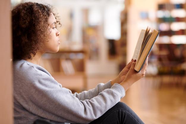 Hübsche junge studentin gemischter rassen in lässigem pullover, die offenes buch vor sich hält, während sie es in der bibliothek liest