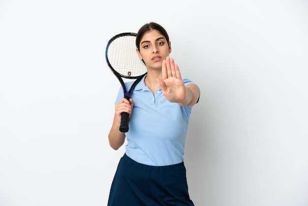 Hübsche junge tennisspielerin kaukasische frau isoliert auf weißem hintergrund, die stop-geste macht
