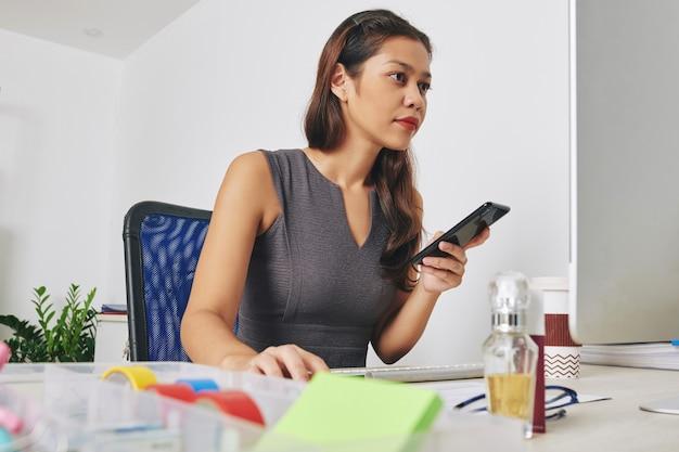 Hübsche junge unternehmerin mit smartphone in der hand, die dokument auf computerbildschirm an ihrem schreibtisch liest