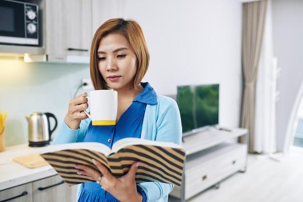 Hübsche junge vietnamesische frau, die interessantes buch genießt und tasse starken kaffee trinkt