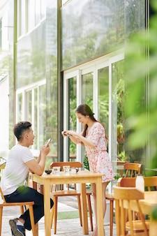 Hübsche junge vietnamesische frau, die sich über kaffeetisch beugt, um foto des frühstücks für ihren blog zu machen