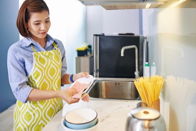 Hübsche junge vietnamesische hausfrau, die teller mit weichem tuch abwischt, nachdem sie das kochen beendet hat