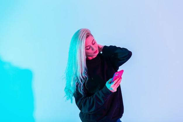 Hübsche junge vorbildliche frau in modischer freizeitkleidung mit telefon auf farbigem neonrosa hellem hintergrund