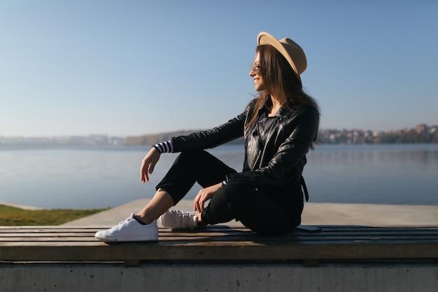 Hübsche junge vorbildliche mädchenfrau, die auf der bank im herbsttag am seeufer am see sitzend aufwirft