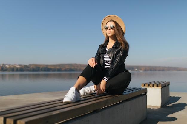 Hübsche junge vorbildliche mädchenfrau sitzen auf einer bank im herbsttag am seeufer, gekleidet in freizeitkleidung