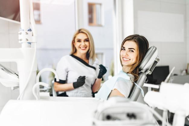 Hübsche junge zahnärztin, die untersuchung und behandlung für junge patientin in der zahnklinik macht.