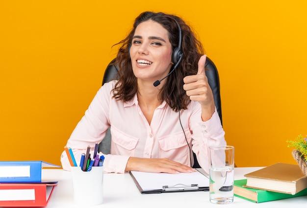 Hübsche kaukasische callcenter-betreiberin mit kopfhörern, die mit bürowerkzeugen am schreibtisch sitzen