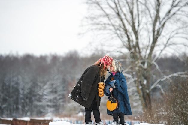 Hübsche kaukasische dorfschwestern stehen mit balalaika auf der bank