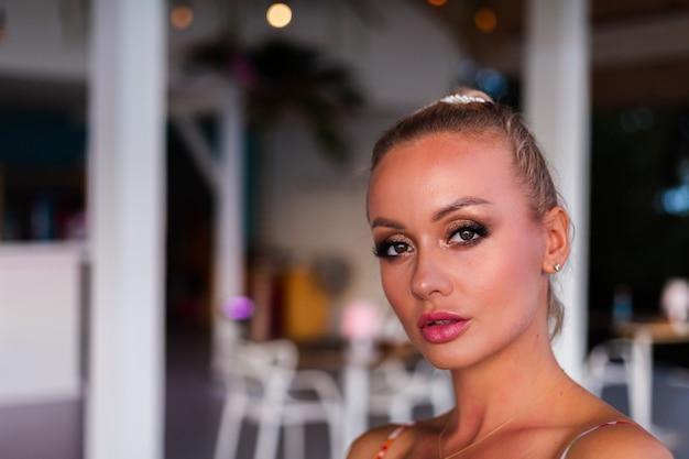 Hübsche kaukasische frau im fliegenden sommerkleid im luxushotelvilla-restaurant im urlaub