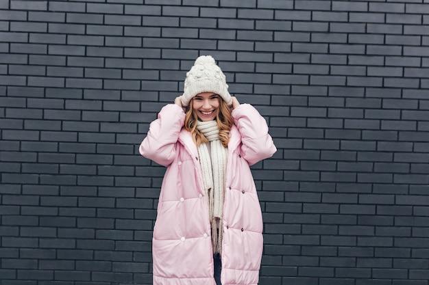 Hübsche kaukasische frau in der winterkleidung, die mit aufrichtigem glücklichem lächeln aufwirft. foto im freien des scherzhaften blonden europäischen mädchens in der strickmütze.