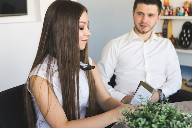 Hübsche kaukasische geschäftsfrau, die mit kunden arbeitet und spricht