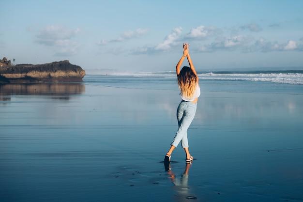 Hübsche kaukasische passende frau im weißen oberteil und in den jeans auf reflektierendem strand durch ozean bei sonnenuntergangslicht