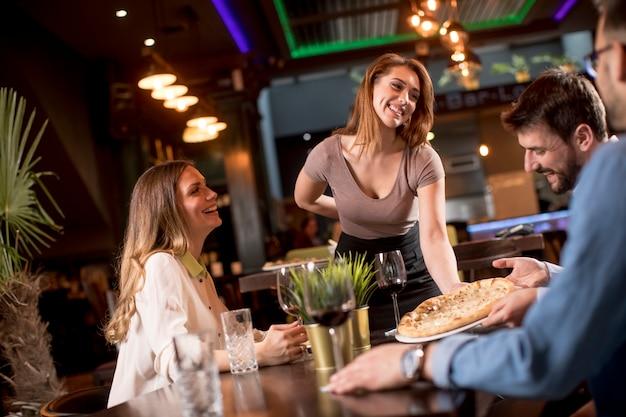 Hübsche kellnerin, die gruppe von freunden mit essen im restaurant dient