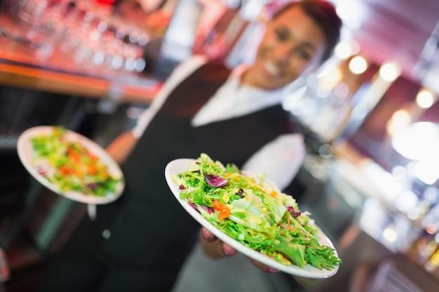 Hübsche kellnerin, die platten von salaten hält