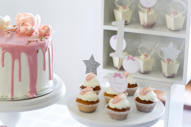 Hübsche kleine kleine kuchen mit weißer creme dienten auf weißem teller