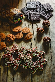 Hübsche komposition mit warmem licht aus weihnachtsbonbons und schokoladenplätzchen