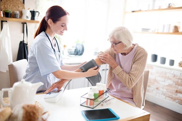 Hübsche krankenschwester, die den druck für grauhaarige rentner misst