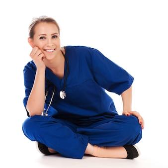 Hübsche krankenschwester, welche die meditation lokalisiert auf weiß tut