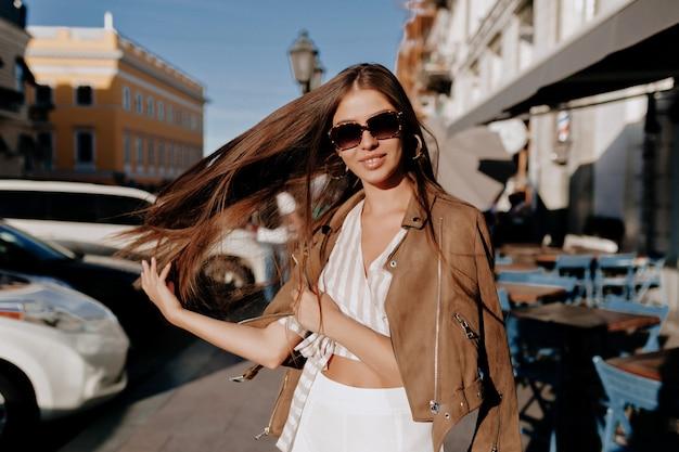 Hübsche lachende frau mit langen haaren hat eine gute zeit im herbstwochenende. außenporträt der liebenswerten trendigen dame, die mit ihren haaren spielt und spaß im sonnenlicht auf allee hat