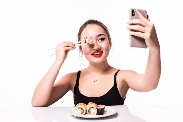 Hübsche lächelnde asiatische frau bedeckt ihr auge mit sushi-rolle und macht selfie auf ihrem handy